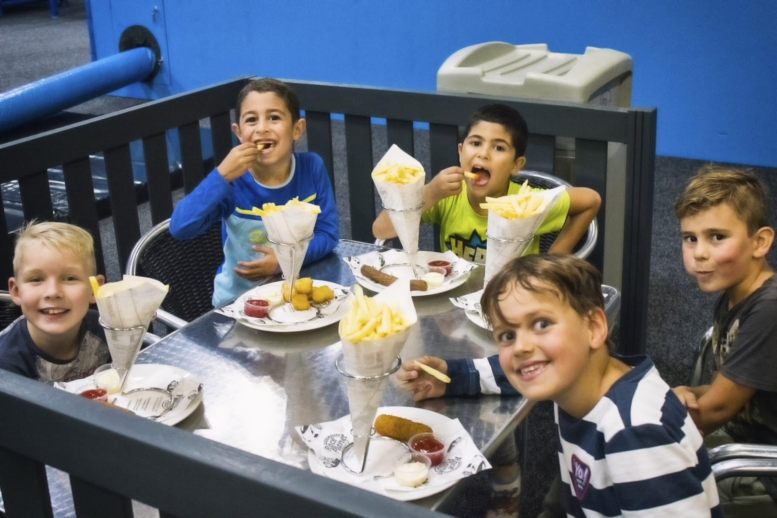 Kinderen eten lekkere patatjes na het spelen bij Jimmy's Speelparadijs.