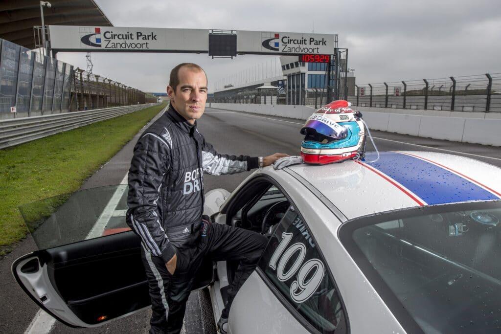 Coureur Jeroen Bleekemolen naast een Race Planet Porsche 911 op Circuit Zandvoort.