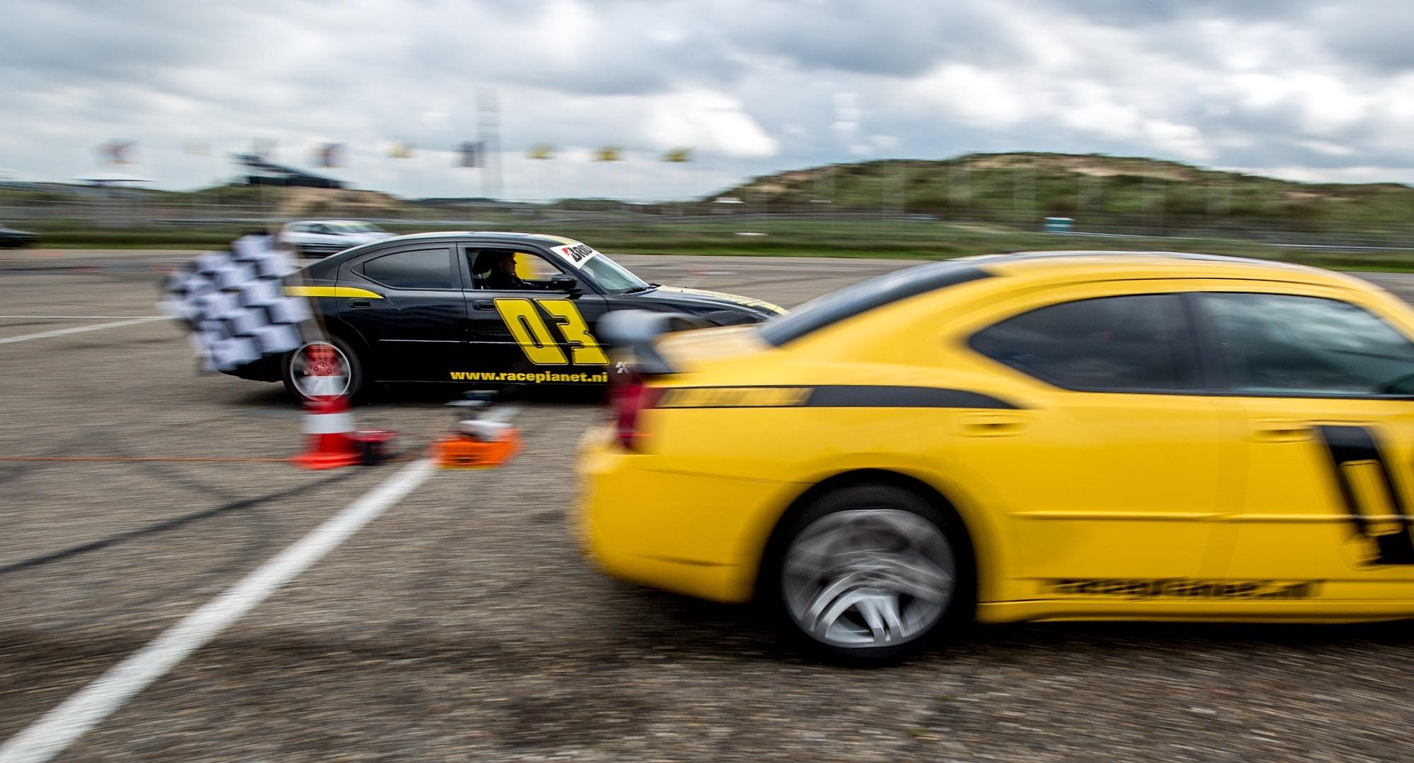 Dragrace tijdens een Race Experience van Bleekemolens Race Planet op Circuit Zandvoort waarbij twee deelnemers tegen elkaar racen in Dodge Chargers.