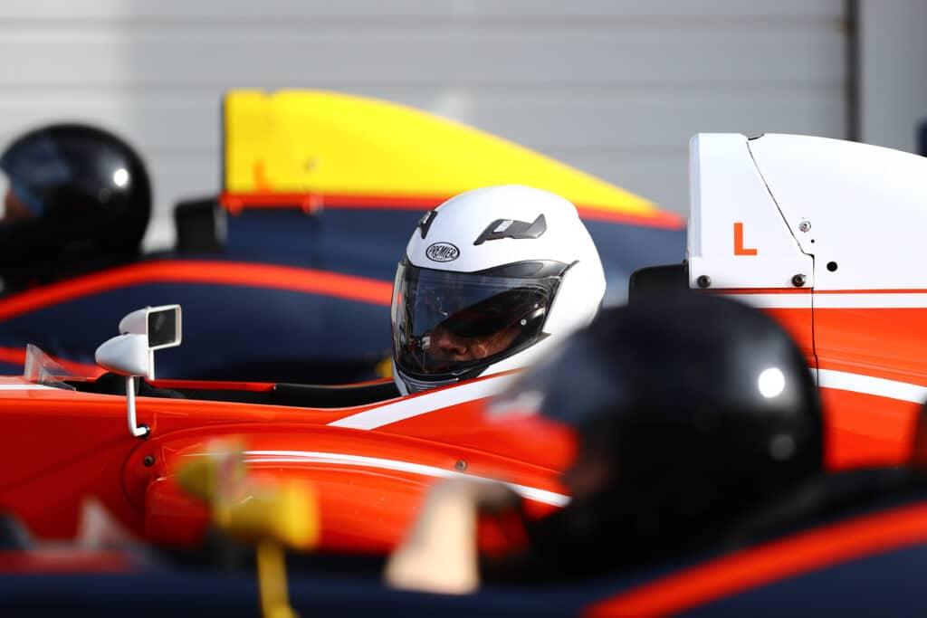 Rijders in Formule RP1 auto's staan klaar in de pitstraat om te gaan rijden.