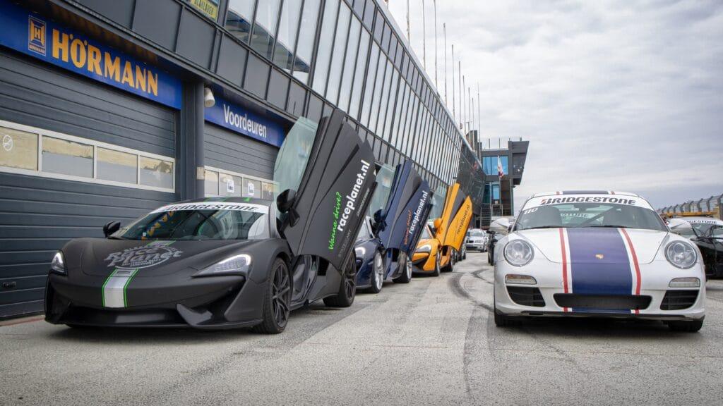 Supercars met McLaren 540c en Porsche 911 staan klaar in de pitstraat van Circuit Zandvoort bij een Race Planet.