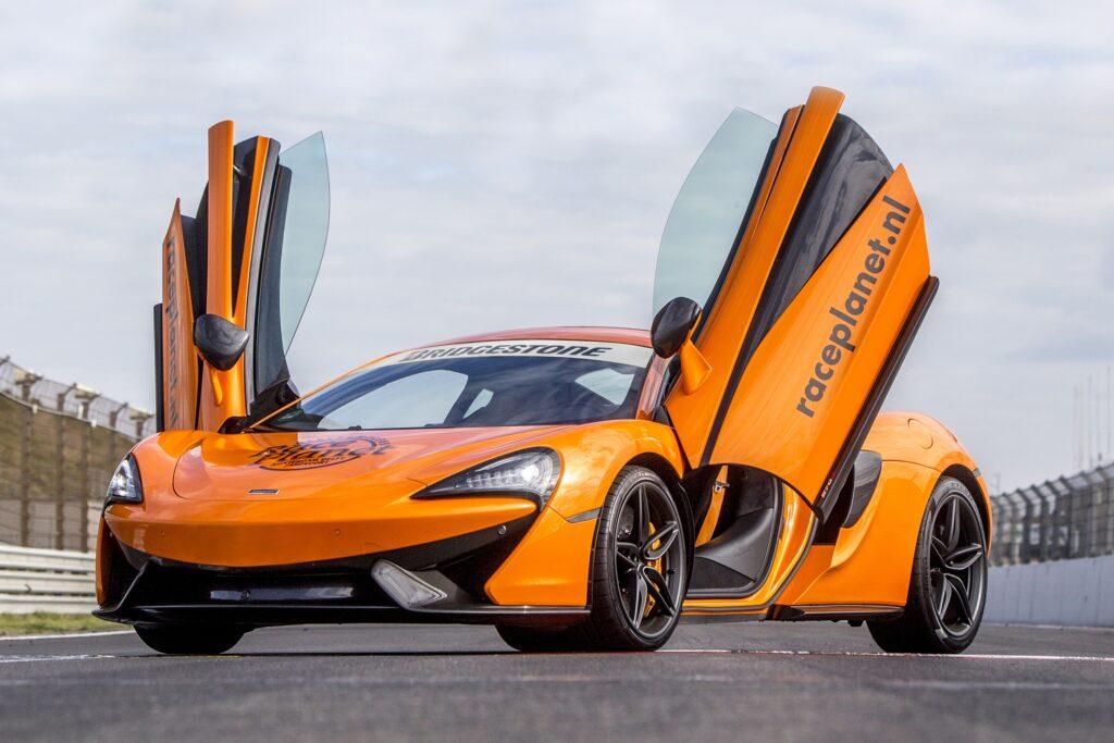 Oranje McLaren 540C met open vleugeldeuren op het rechte stuk van Circuit Zandvoort.