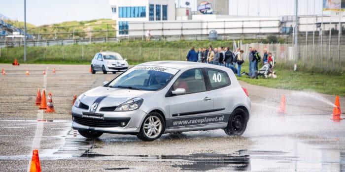 Renault Clio breekt uit in de bocht tijdens de slipproef op nat asfalt tijdens een Race Experience van Race Planet op Circuit Zandvoort.
