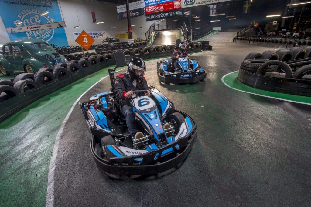 Karters racen tegen elkaar op de kartbanen van Race Planet in Amsterdam en Delft