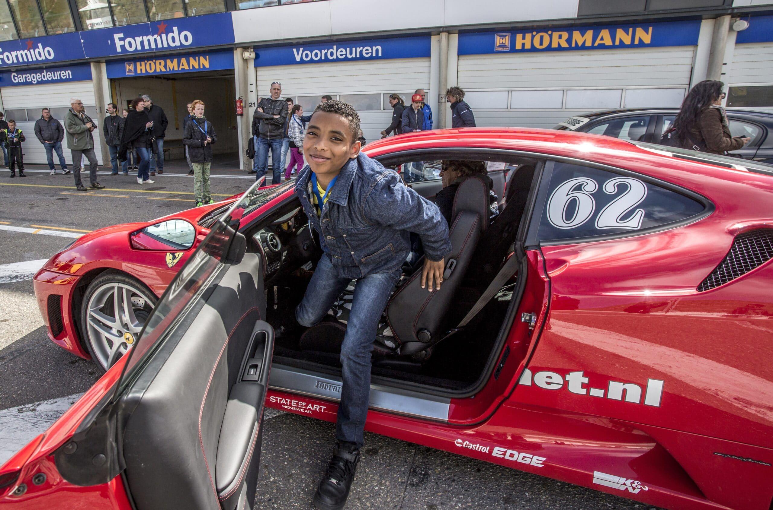 Jongen stapt uit een Ferrari tijdens het Autorijden voor de Jeugd op Circuit Zandvoort bij Race Planet.