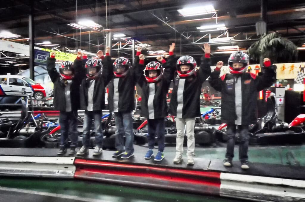 Kinderen juichen op de kartbaan na het karten bij Race Planet Delft en Amsterdam.
