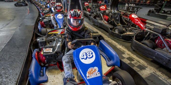 Kinderen zitten in een kart klaar voor de Kart cursus bij Race Planet in Amsterdam en Delft op de kartbaan.